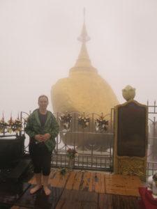 Eine Person steht barfuß. Hinter ihr ist Nebel, durch den der Goldene Felsen hervorscheint