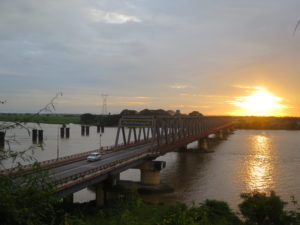 Functioning bridge as well as left-overs of a blown-up own, across a river, at sunset